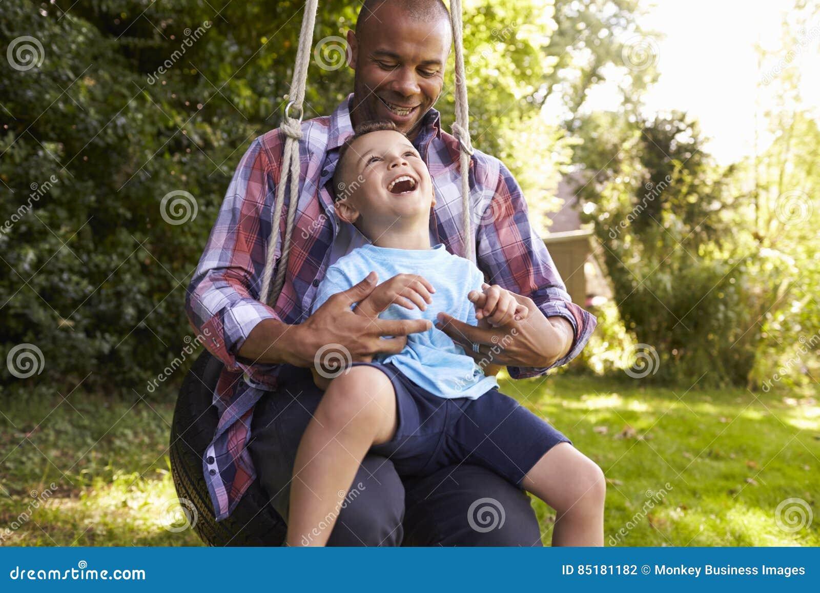 Πατέρας και γιος που έχουν τη διασκέδαση στην ταλάντευση ροδών στον κήπο