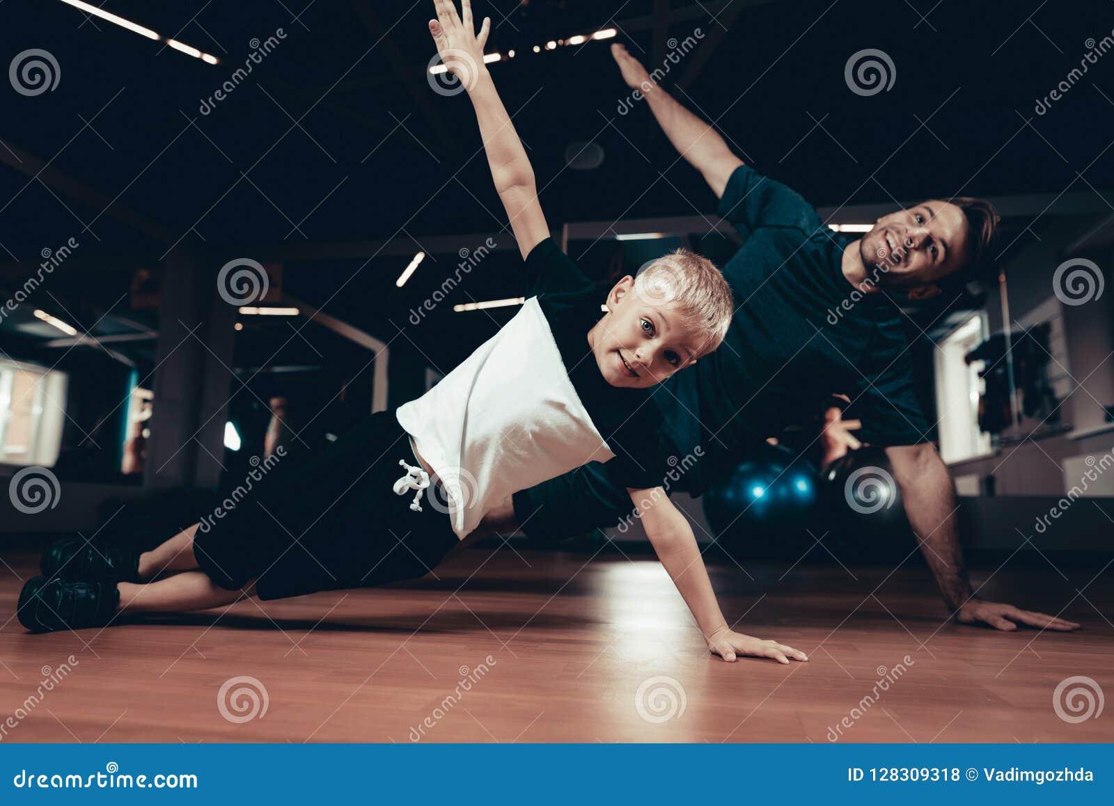 Πατέρας και γιος που κάνουν τις ασκήσεις Τύπου στη γυμναστική