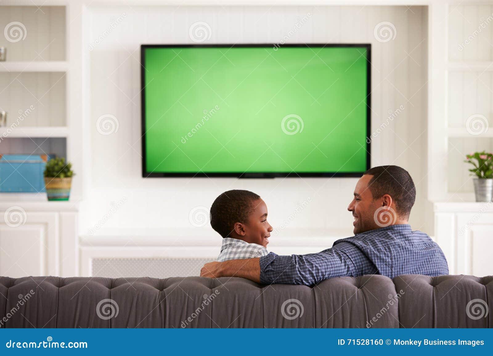 Πατέρας και γιος που προσέχουν τη TV ο ένας τον άλλον, πίσω άποψη
