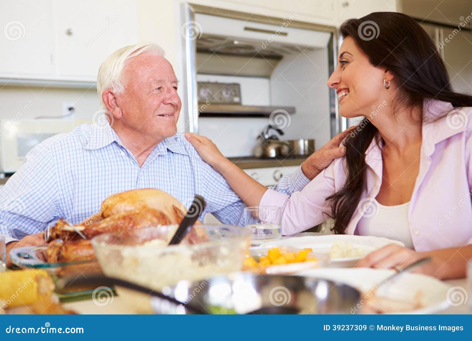 Πατέρας και ενήλικη κόρη που έχουν το οικογενειακό γεύμα στον πίνακα