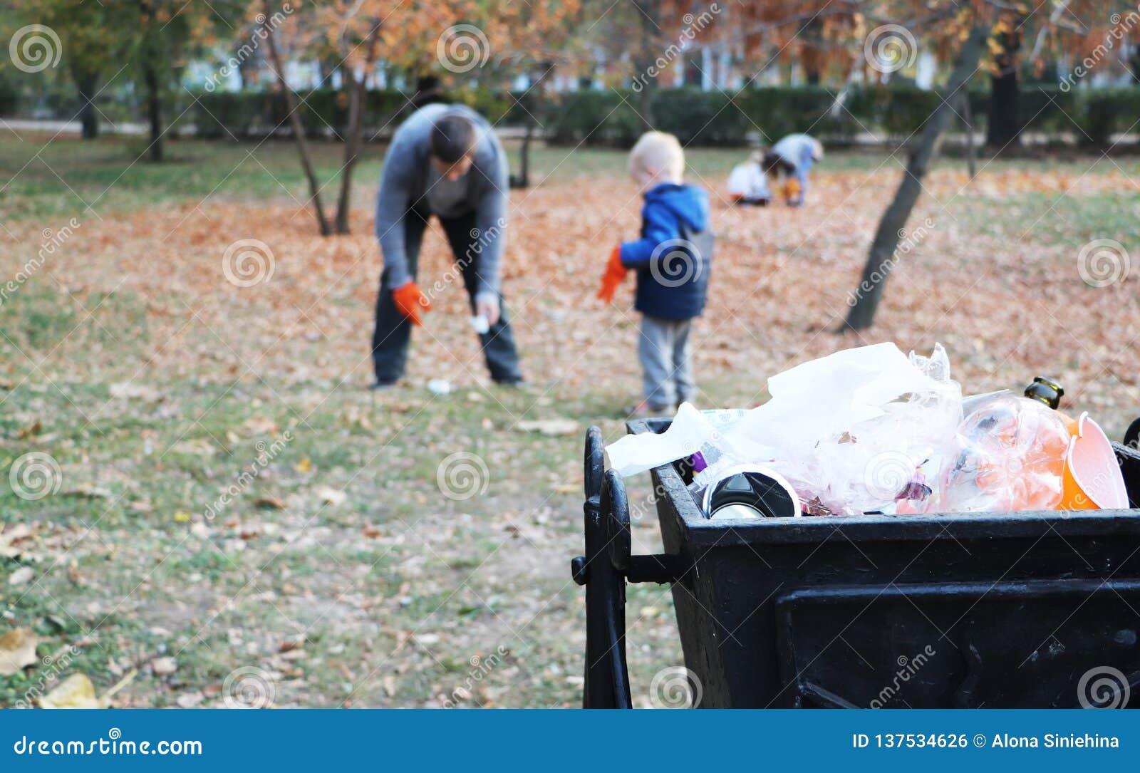 Πατέρας και λίγος γιος που σαρώνουν στο πάρκο Υπόβαθρο - δοχείο απορριμμάτων και απορριμάτων Η έννοια της οικολογίας και της προσ