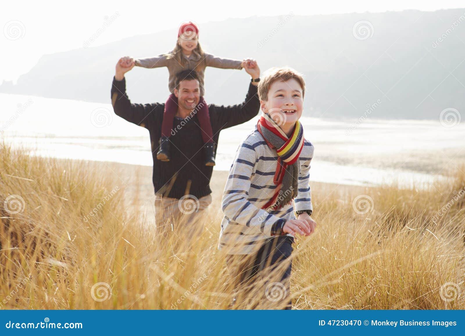 Πατέρας και παιδιά που περπατούν μέσω των αμμόλοφων στη χειμερινή παραλία