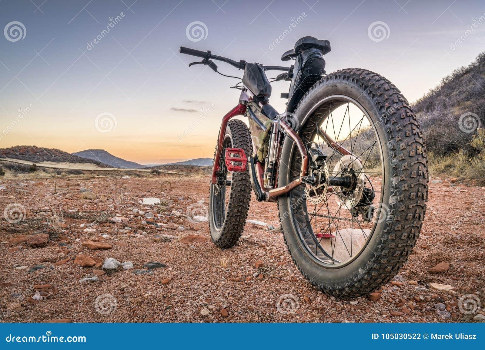 Παχύ ποδήλατο σε ένα ίχνος ερήμων με το βαθύ, χαλαρό αμμοχάλικο