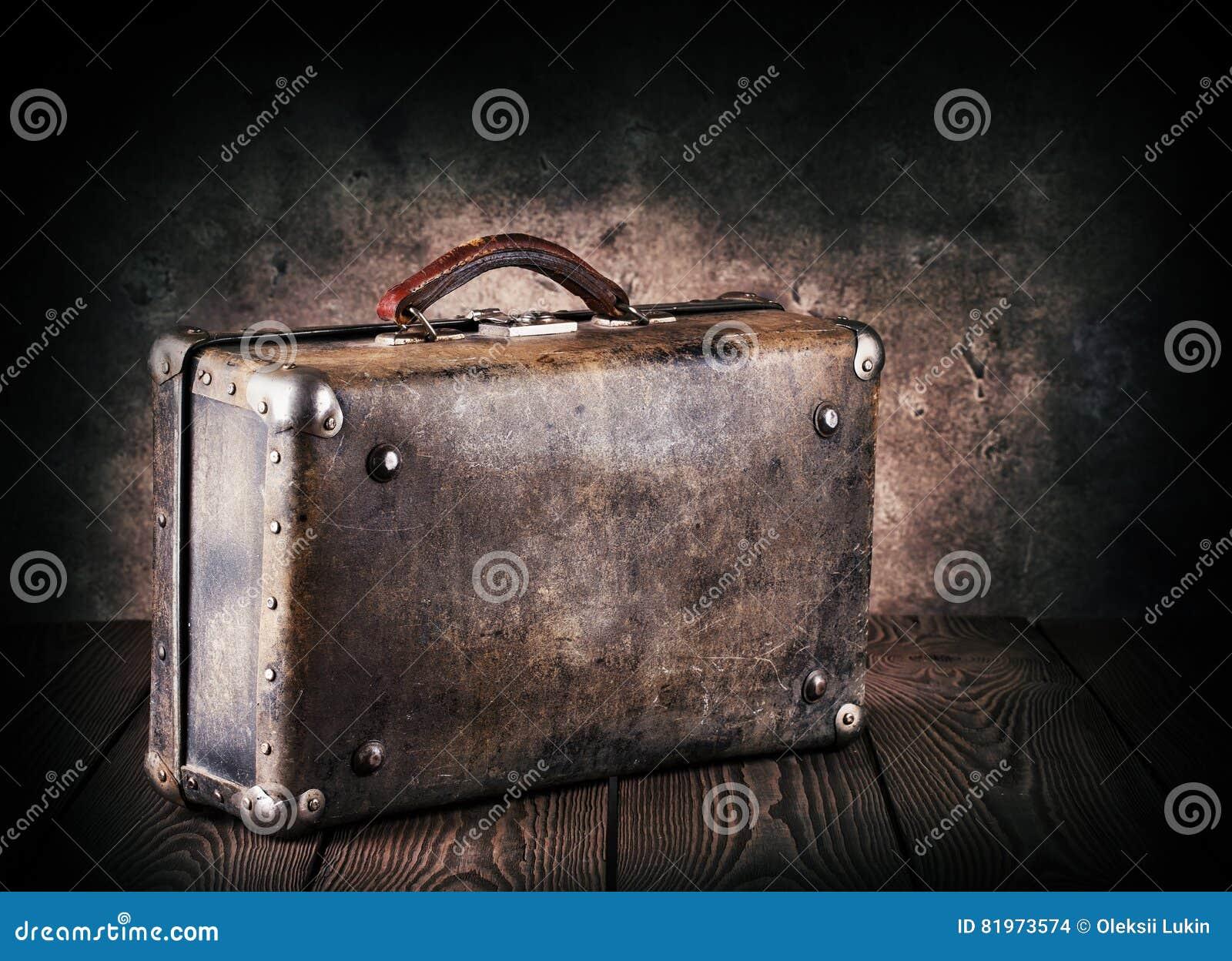 Παλαιά βαλίτσα δέρματος σε έναν ξύλινο πίνακα