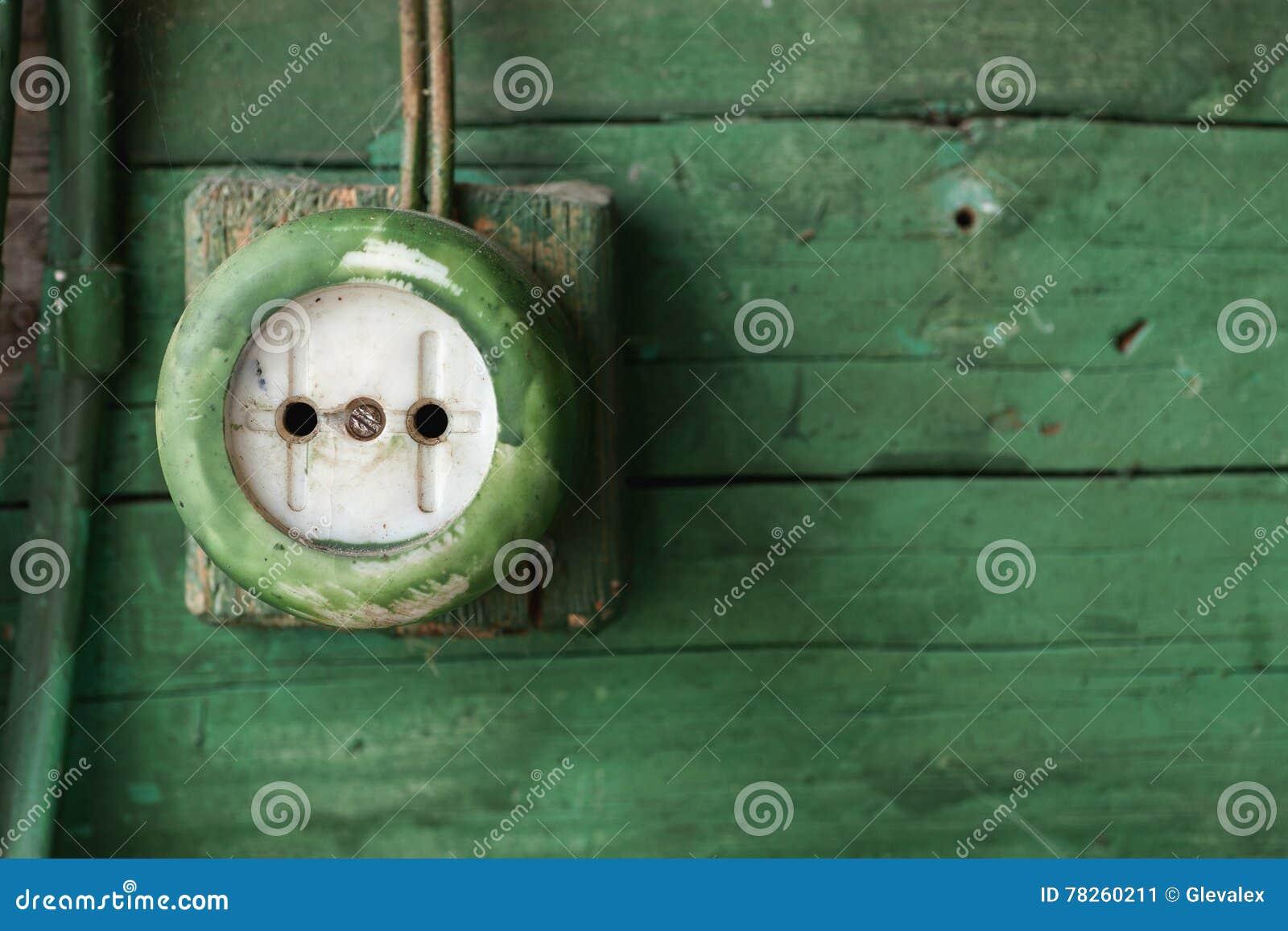 Παλαιά ηλεκτρική έξοδος στον πράσινο ξύλινο τοίχο