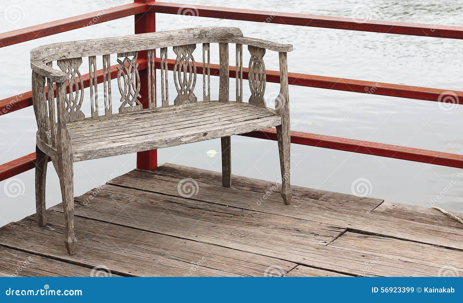 Παλαιά ξύλινη αποβάθρα με τις ξύλινες καρέκλες επίσης