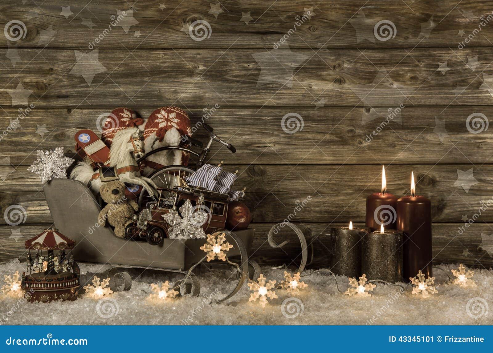 Παλαιά παιχνίδια παιδιών και τέσσερα καίγοντας κεριά εμφάνισης στο ξύλινο vint