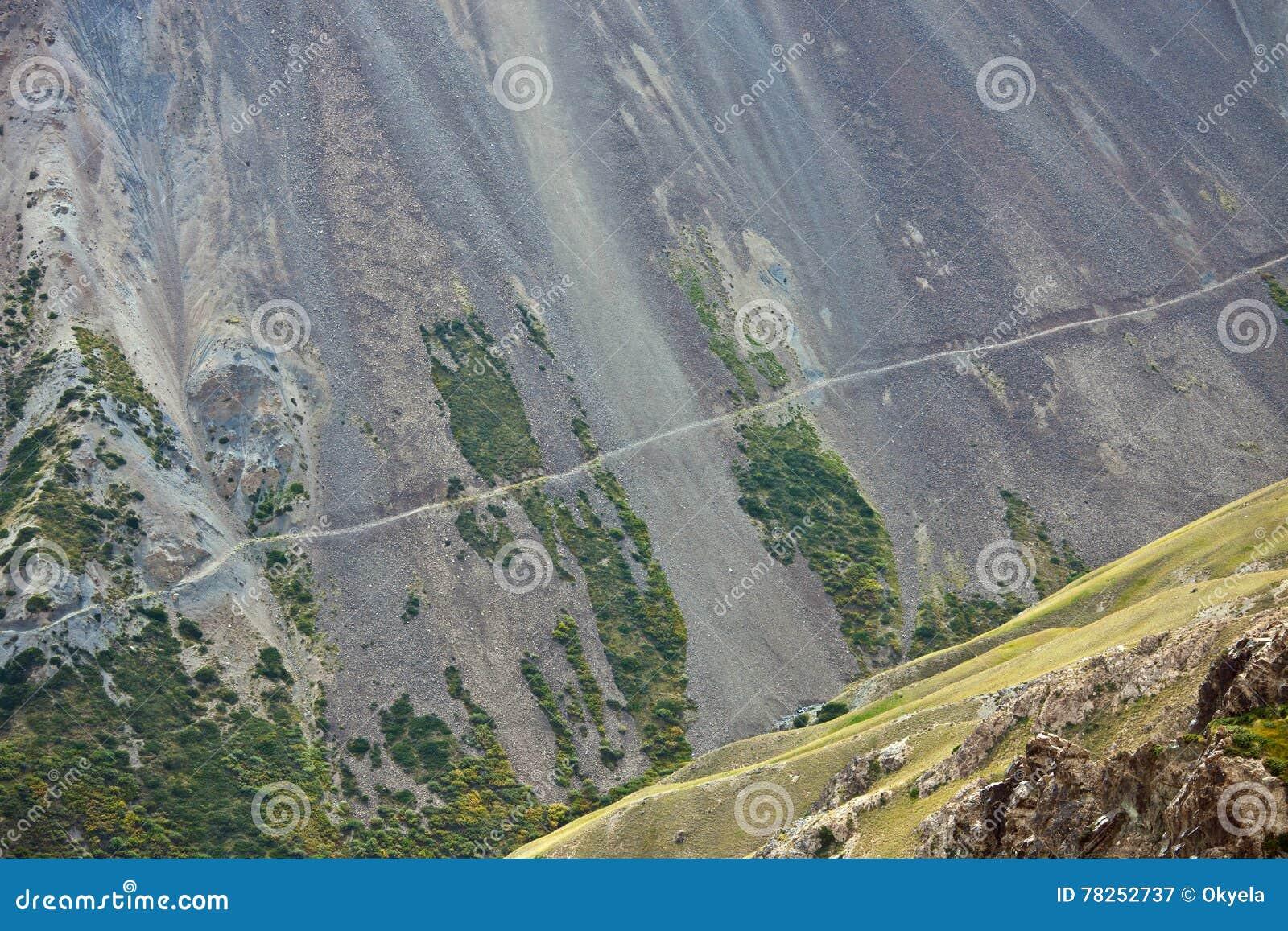 Παλαιός εγκαταλειμμένος δρόμος κατά μήκος μιας απότομης βουνοπλαγιάς με τους δύσκολους βράχους σε λόφο