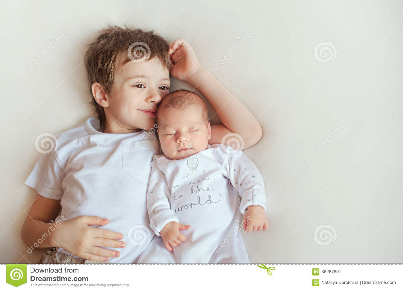 Παλαιότερος αδελφός που αγκαλιάζει τη νεογέννητη αδελφή του Παιδιά στα φωτεινά ενδύματα σε ένα άσπρο κάλυμμα