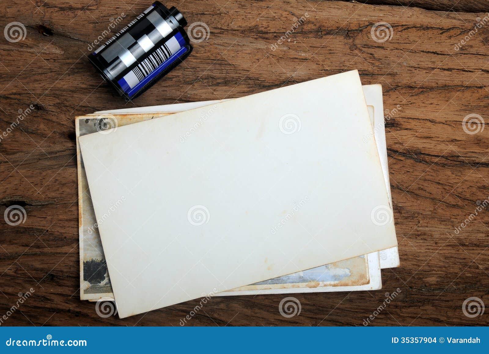 Παλαιό πλαίσιο φωτογραφιών εγγράφου με την ταινία καμερών στο ξύλινο υπόβαθρο
