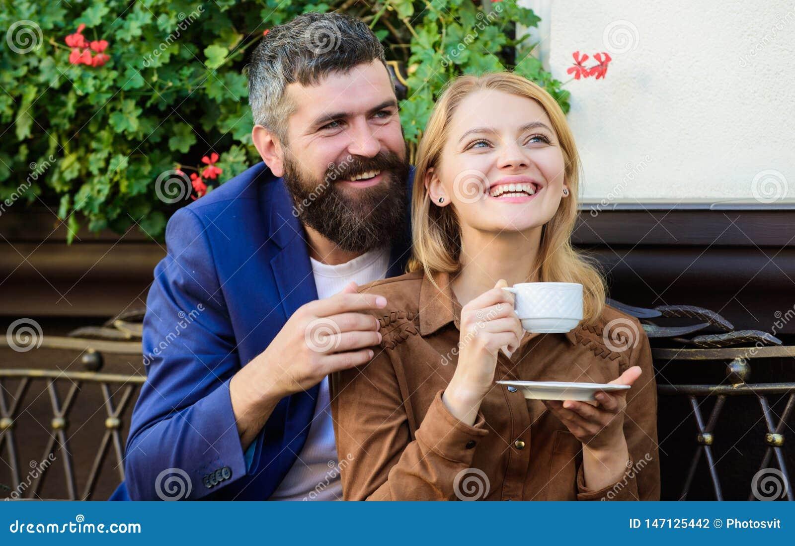 Πεζούλι καφέδων αγκαλιάς ζεύγους Το ζεύγος ερωτευμένο κάθεται το πεζούλι καφέδων αγκαλιάσματος απολαμβάνει τον καφέ Ευχάριστο οικ