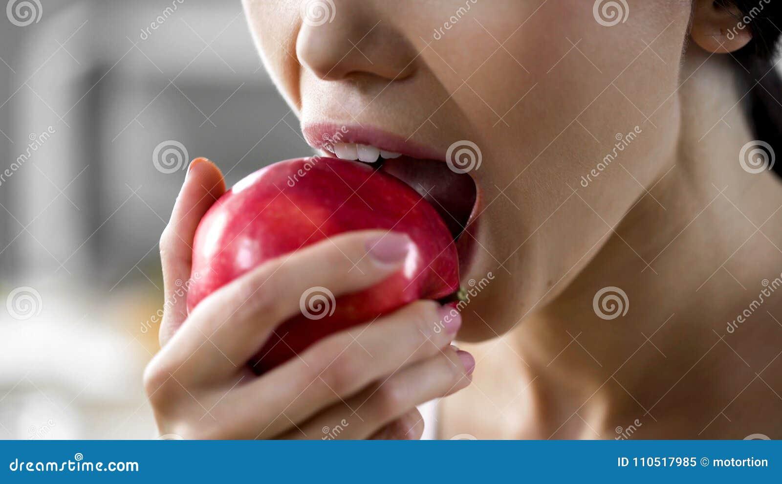 Πεινασμένο κορίτσι με τη μεγάλη όρεξη που δαγκώνει το μεγάλο juicy μήλο, υγιές πρόχειρο φαγητό στην εργασία