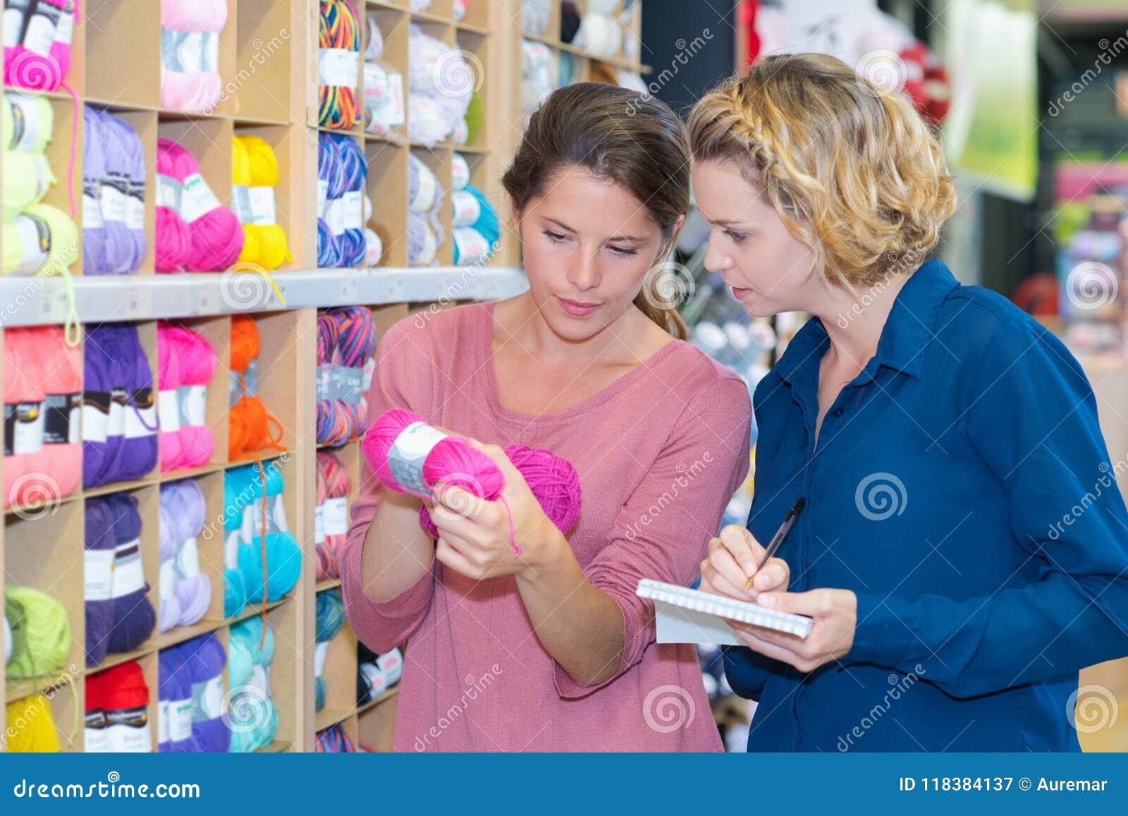 Πελάτης γυναικών που επιλέγει το διάφορο νήμα στο ράψιμο του καταστήματος