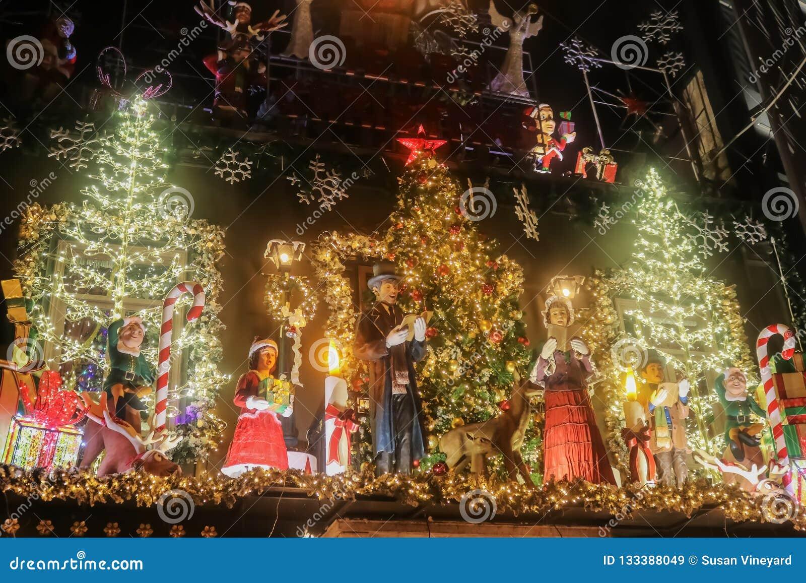 Περίκομψη αναμμένη επάνω επίδειξη Χριστουγέννων τη νύχτα επάνω από λίγο κατάστημα Kooks κεντρικός με τα δέντρα και τα carolers