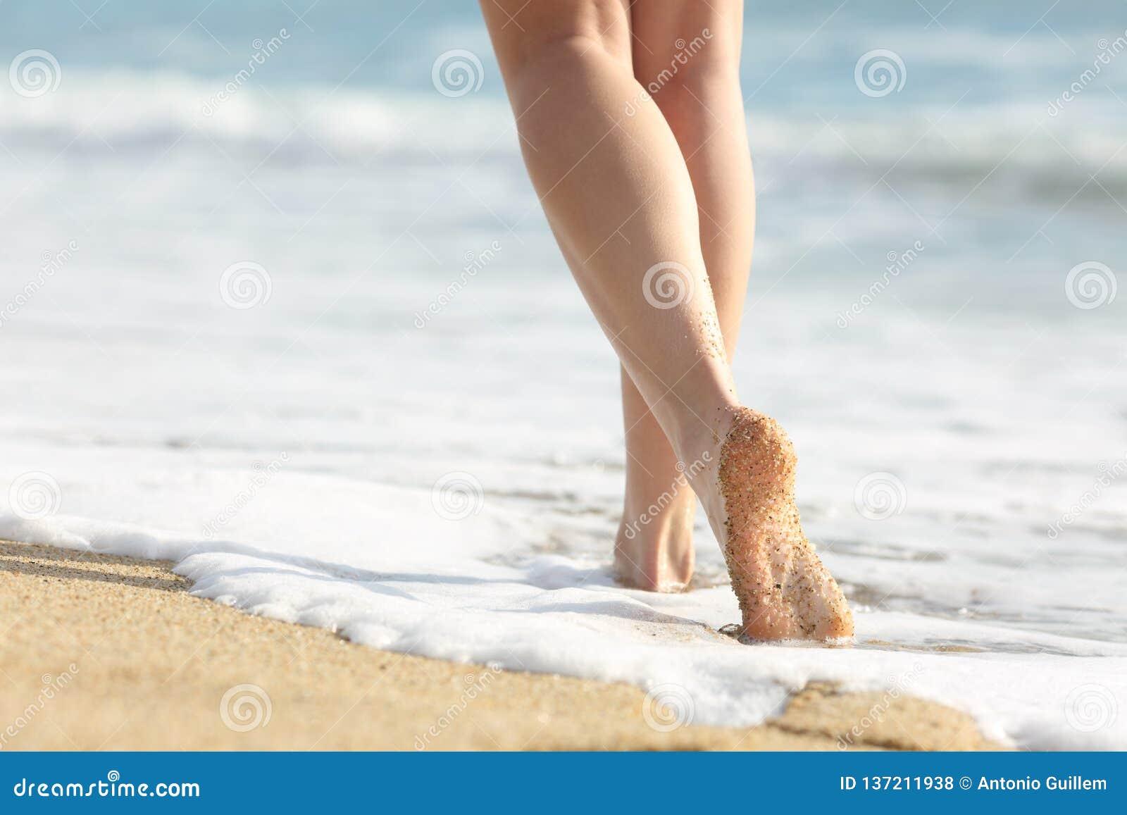 Περίπατοι ποδιών κοριτσιών στην άμμο και θαλάσσιο νερό στην παραλία