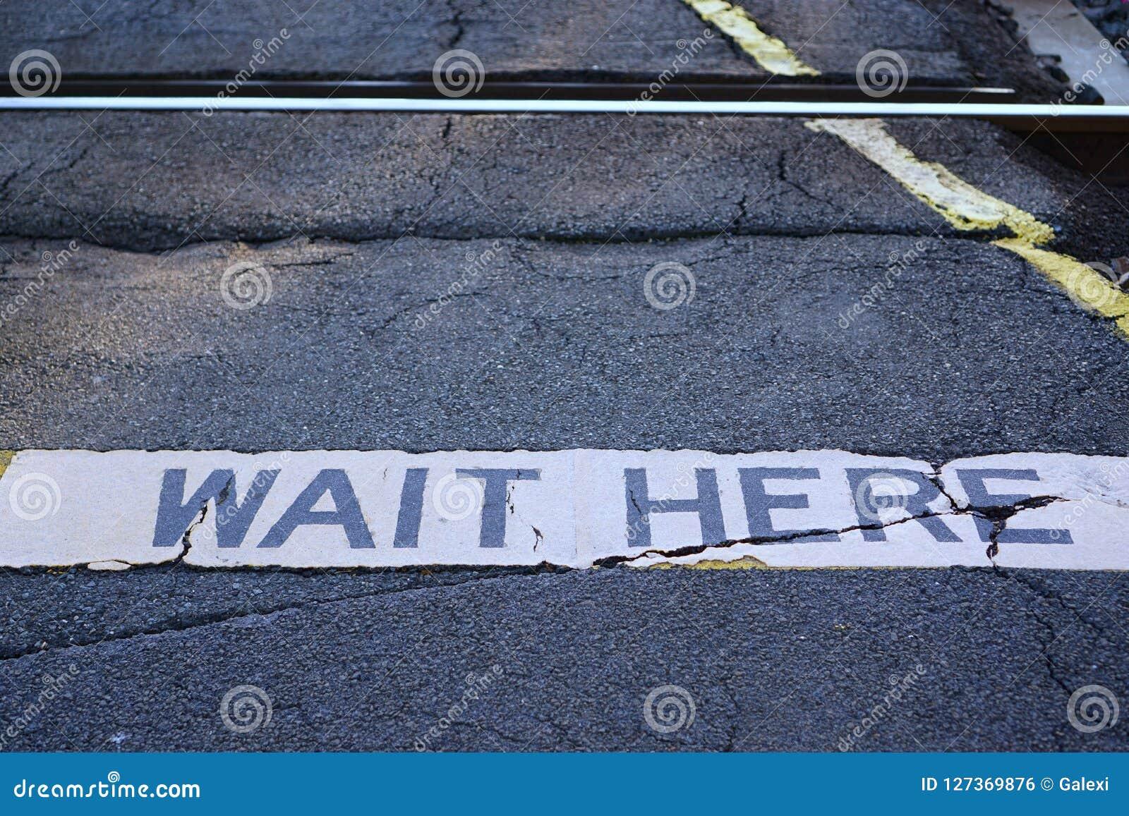 Περιμένετε εδώ το σημάδι στο πέρασμα σιδηροδρόμων