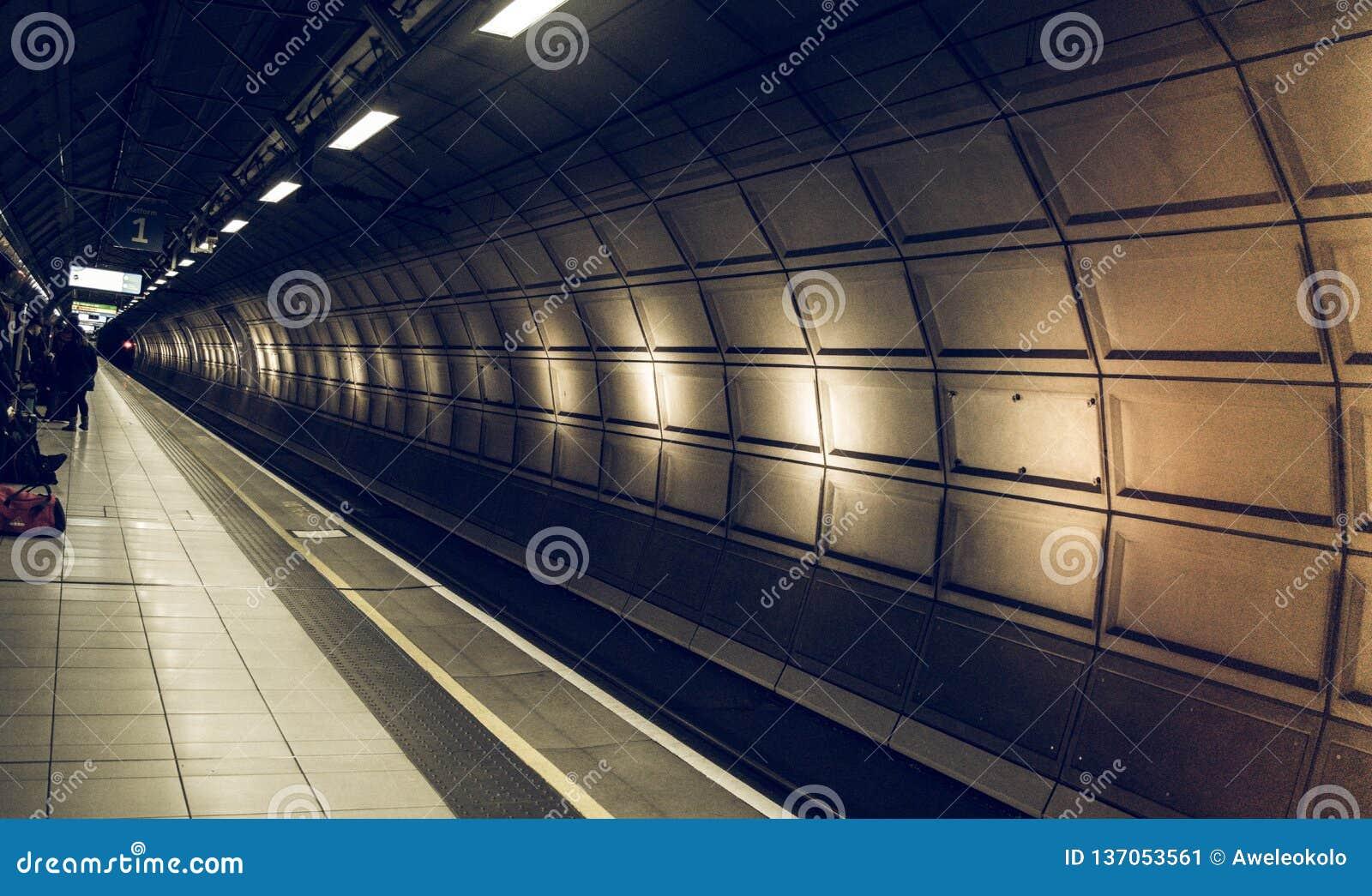Περιμένοντας στον όμορφο σιδηροδρομικό σταθμό η σήραγγα δεν σταματά κανένα τραίνο στον αερολιμένα άφιξης Heathrow, Λονδίνο Σιδηρό