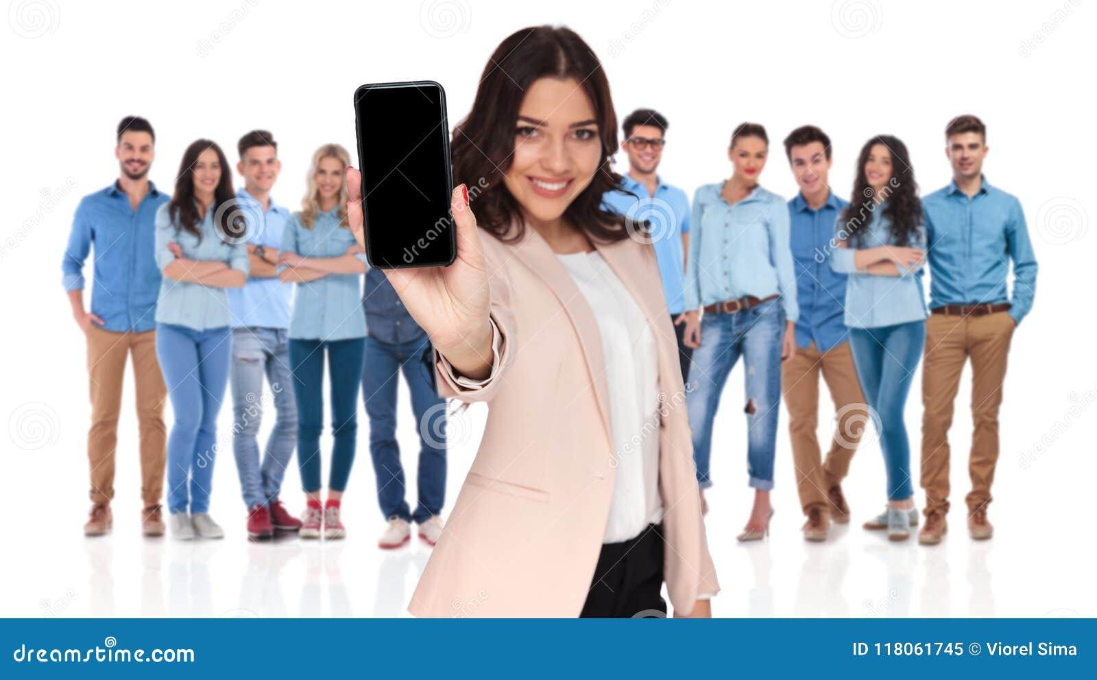 Περιστασιακή ομάδα με τον ηγέτη επιχειρηματιών που παρουσιάζει τηλεφωνική οθόνη ι