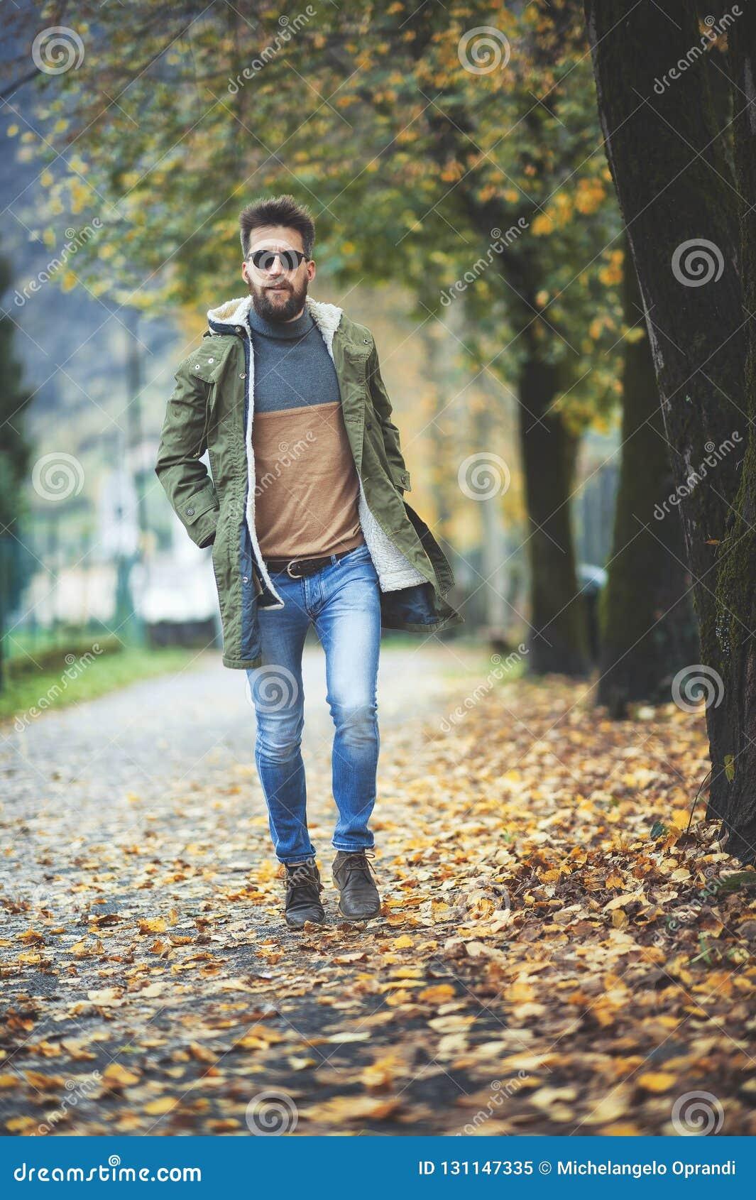 Περιστασιακό άτομο ύφους χίπηδων που περπατά μεταξύ των φύλλων φθινοπώρου