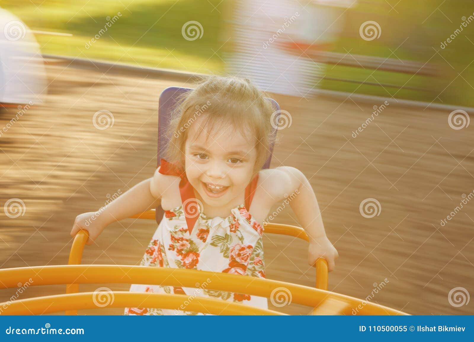 Περιστροφή μικρών κοριτσιών σε ένα ιπποδρόμιο παιδιών ` s μεταξύ της παιδικής χαράς