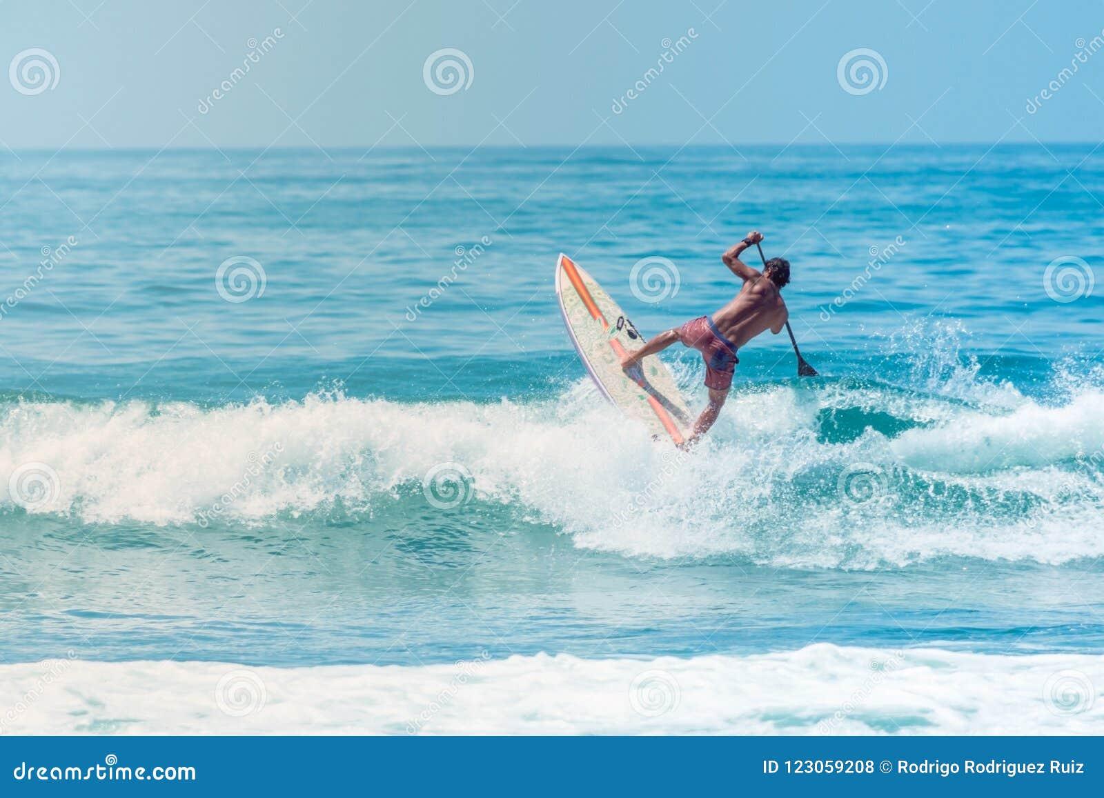 Πηδώντας κύμα Surfer με έναν πίνακα στην παραλία Sayulita Nayarit