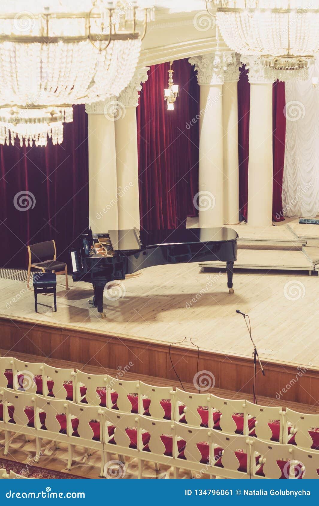 Πιάνο στη σκηνή και κενές καρέκλες στη αίθουσα συναυλιών