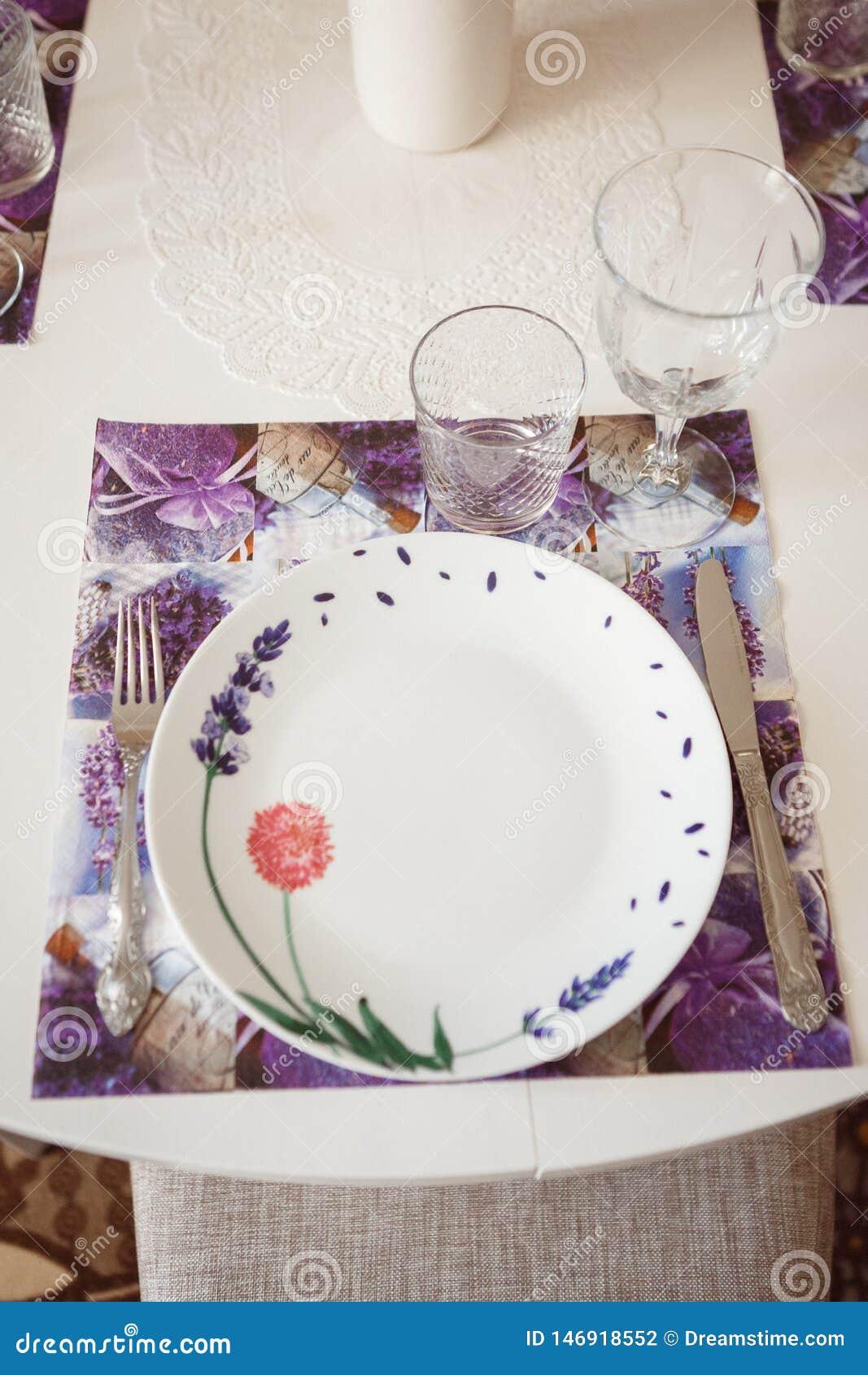 Πιάτο, δίκρανο και γυαλιά σε μια ιώδη πετσέτα