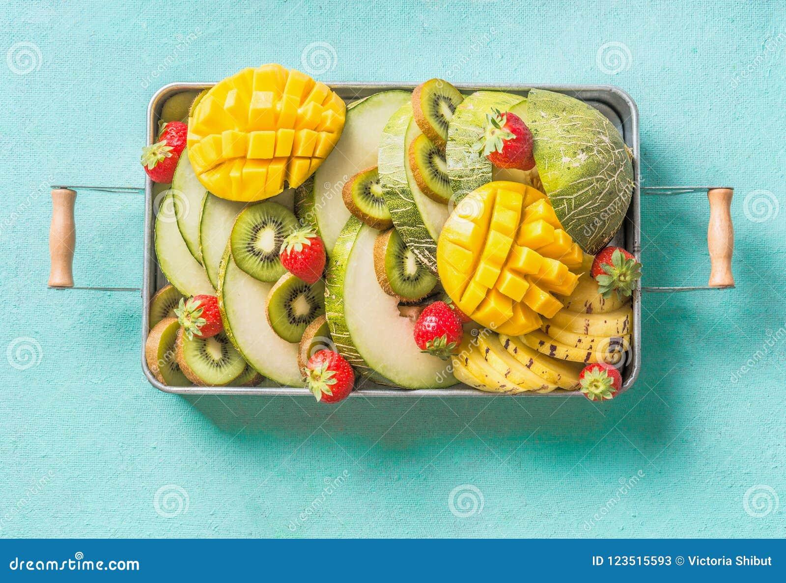 Πιάτο θερινών φρούτων και μούρων στο ανοικτό μπλε υπόβαθρο Εξωτική θερινή διατροφή