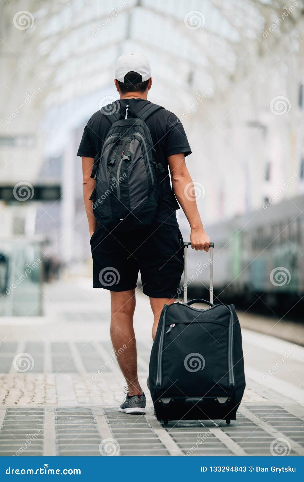 Πλήρες πορτρέτο μήκους ενός ευτυχούς νεαρού άνδρα που περπατά με τη βαλίτσα στο σταθμό τρένου μικρό ταξίδι χαρτών του Δουβλίνου έ