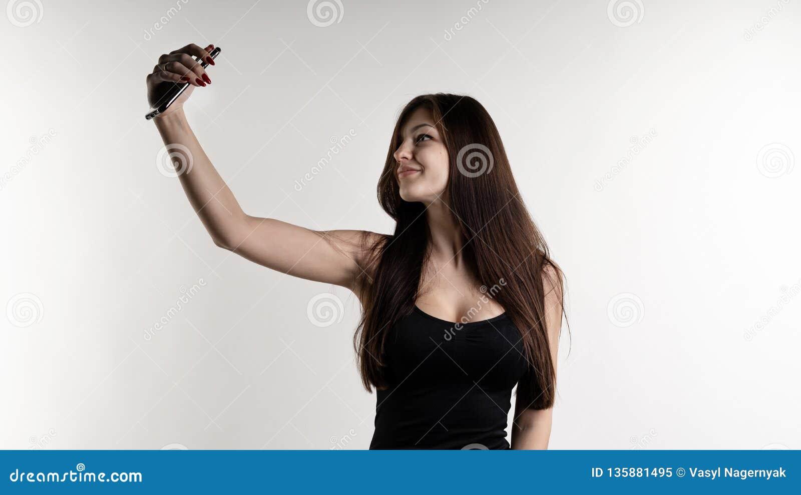 Πλήρες πορτρέτο μήκους μιας εύθυμης νέας όμορφης γυναίκας που κάνει selfie χρησιμοποιώντας το κινητό τηλέφωνο πέρα από το άσπρο υ