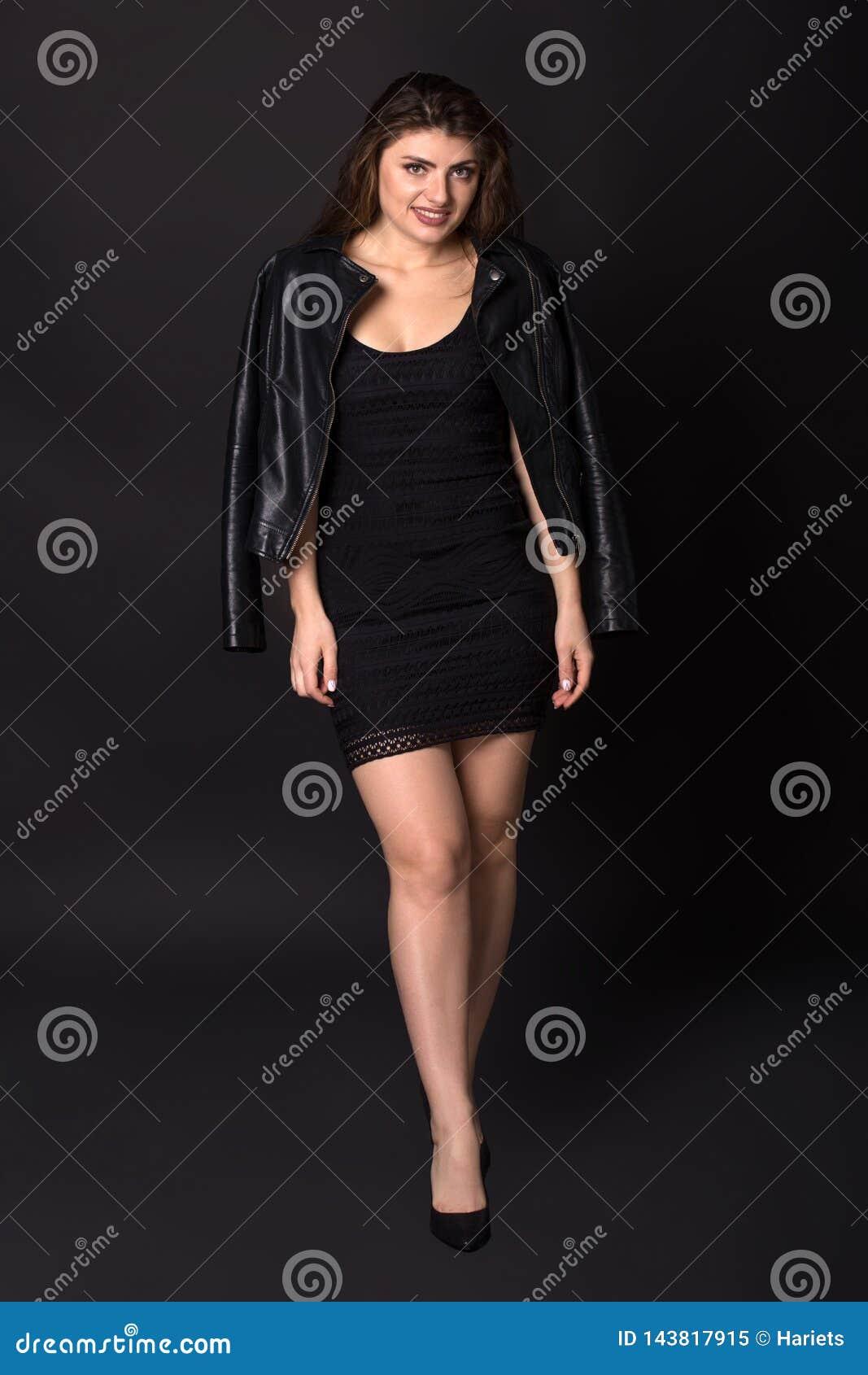 Πλήρες πορτρέτο μήκους της προκλητικής καυκάσιας νέας γυναίκας στο σακάκι δέρματος και το απότομα μαύρο φόρεμα, που θέτει πέρα απ