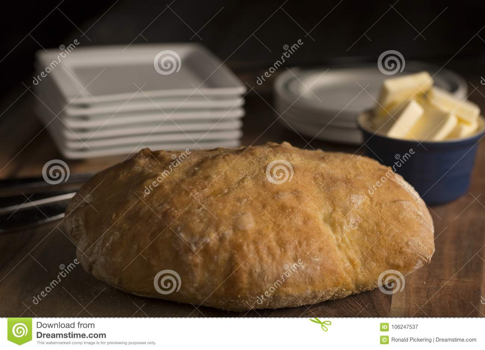 Πλήρης φραντζόλα ψωμιού Pugliese αγροτική ιταλική με το βούτυρο σε έναν ξύλινο τέμνοντα πίνακα