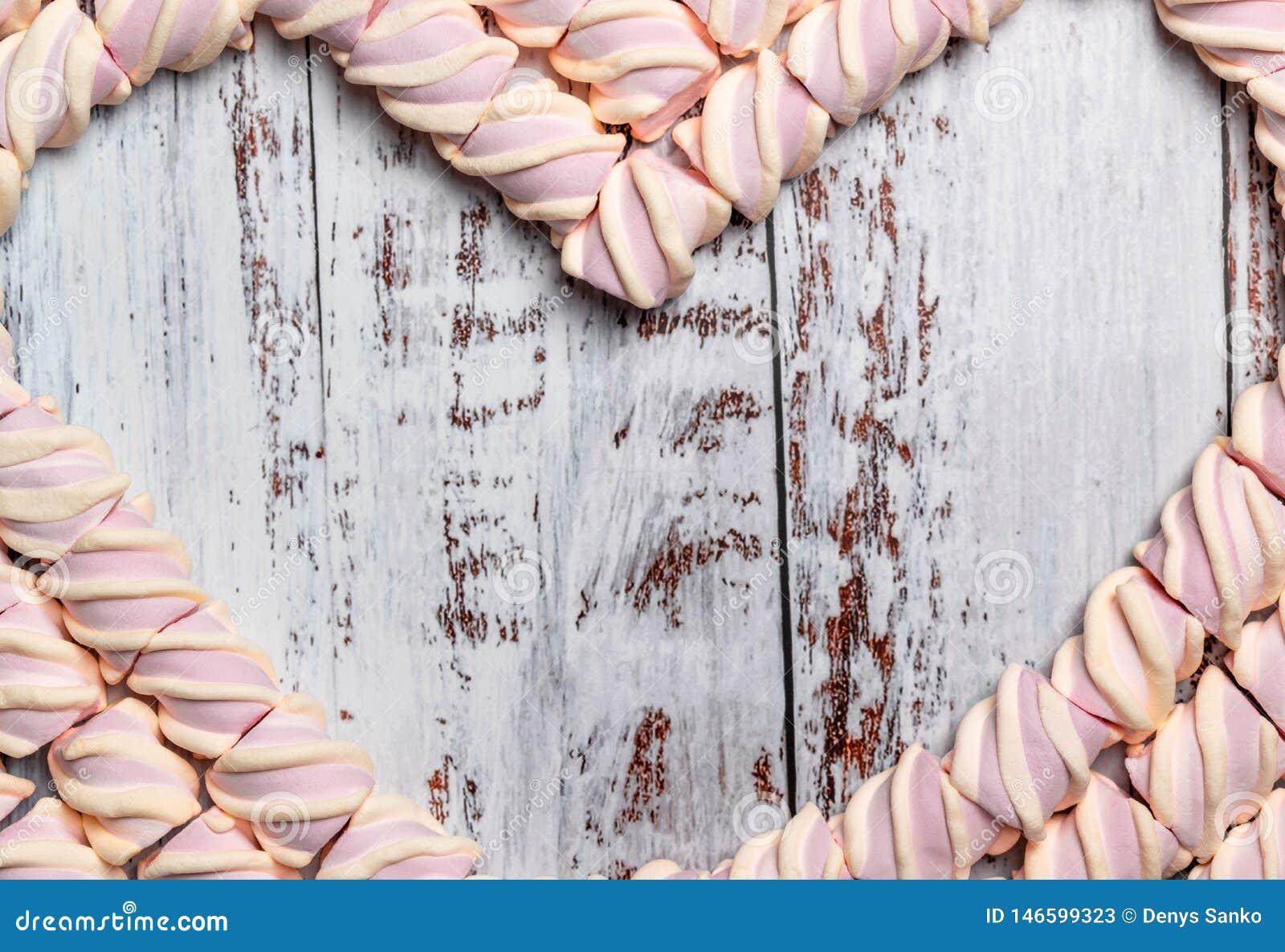 Πλαίσιο με μορφή μιας καρδιάς από marshmallow σε ένα ελαφρύ ξύλινο υπόβαθρο r
