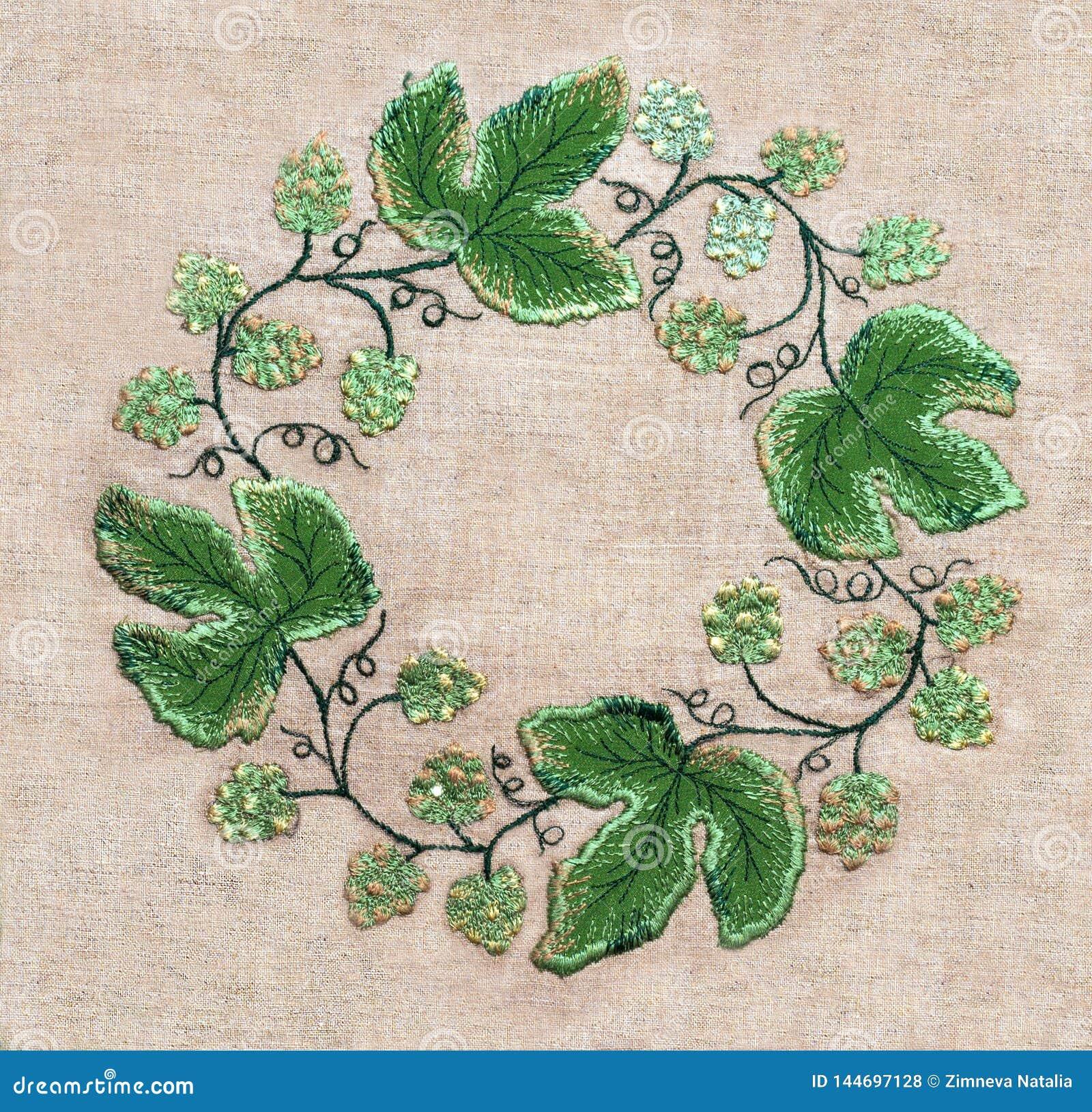 Πλαίσιο των πράσινων φύλλων και των λουλουδιών κεντητικής