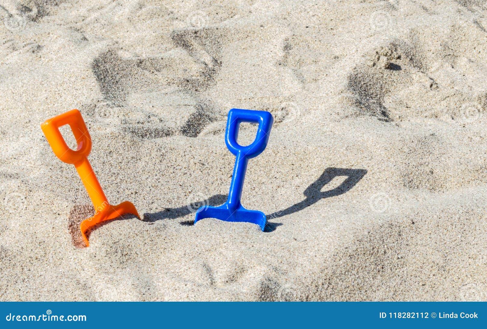 2 πλαστικά φτυάρια σε μια αμμώδη παραλία μια ηλιόλουστη θερινή ημέρα