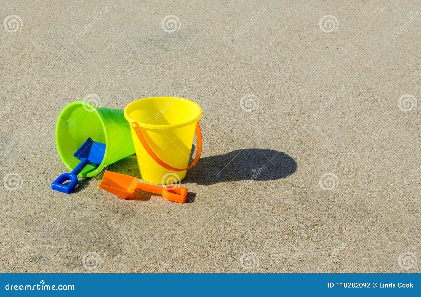 2 πλαστικοί κάδοι και φτυάρια άμμου σε μια ομαλή αμμώδη παραλία