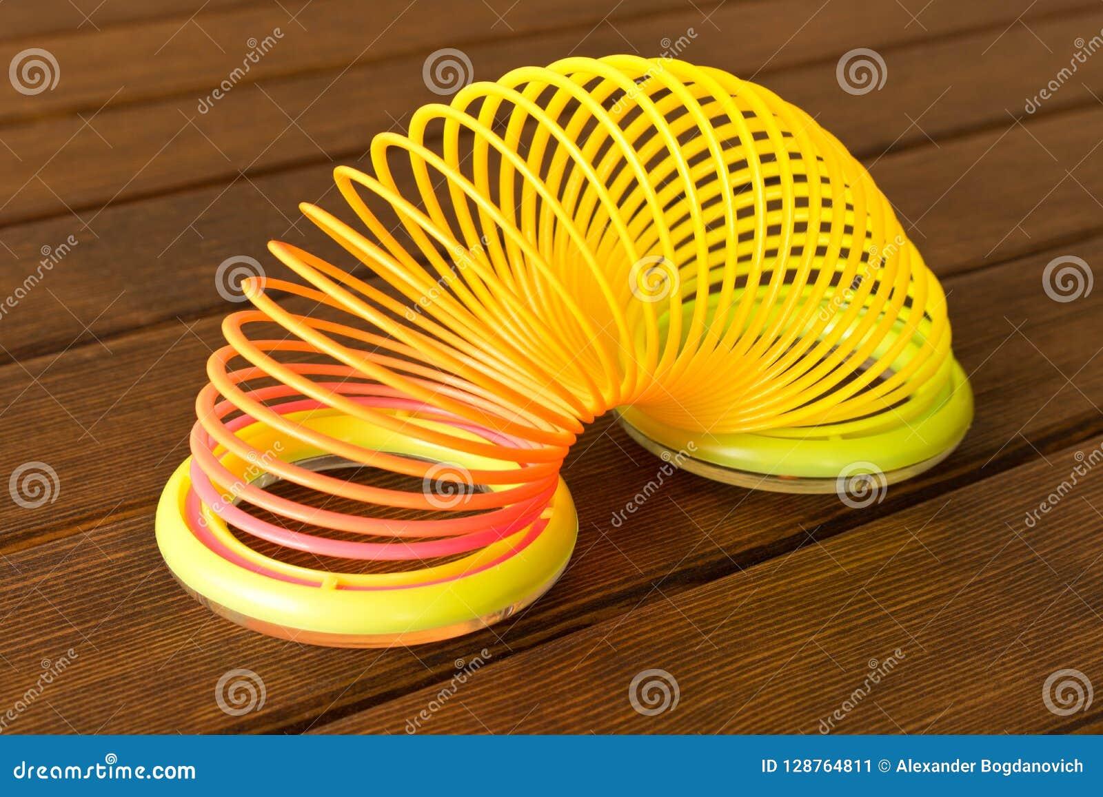 Πλαστικό ουράνιο τόξο παιχνιδιών σε έναν ξύλινο πίνακα Πολύχρωμη σπείρα για