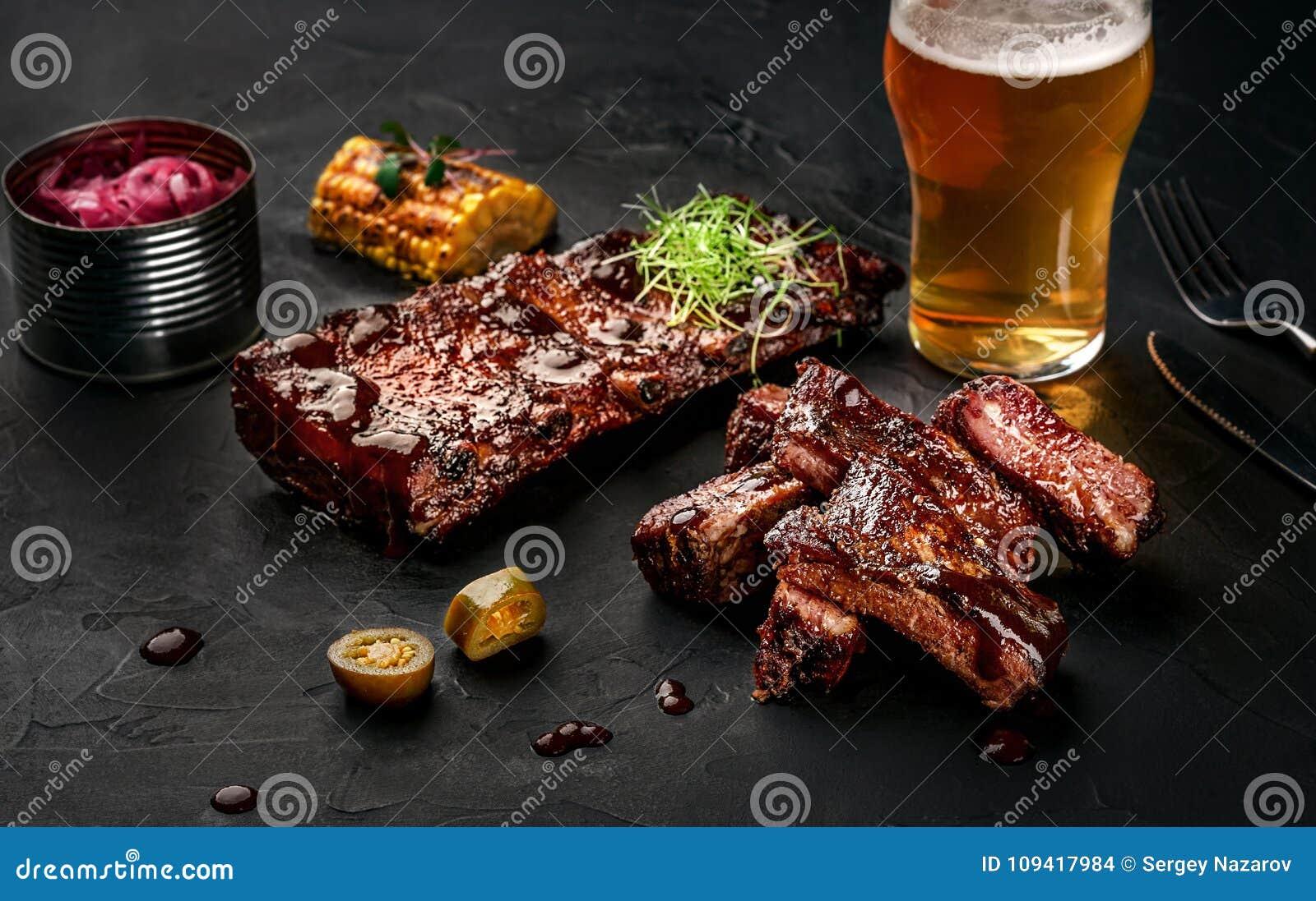 Πλευρά χοιρινού κρέατος στη σάλτσα σχαρών και ένα ποτήρι της μπύρας σε ένα μαύρο πιάτο πλακών Ένα μεγάλο πρόχειρο φαγητό στην μπύ
