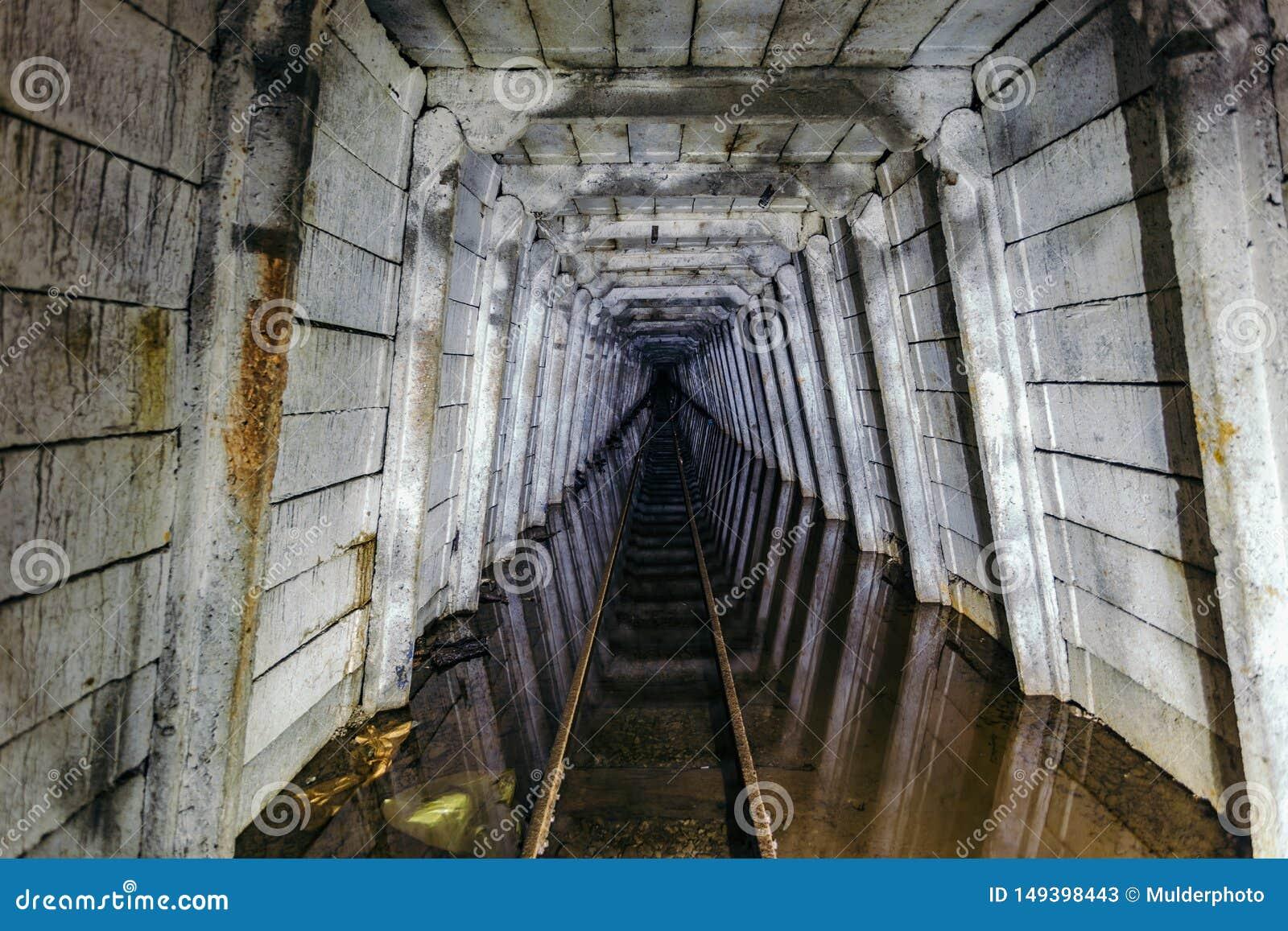 Πλημμυρισμένο εγκαταλειμμένο ορυχείο ουράνιου με το σκουριασμένο σιδηρόδρομο
