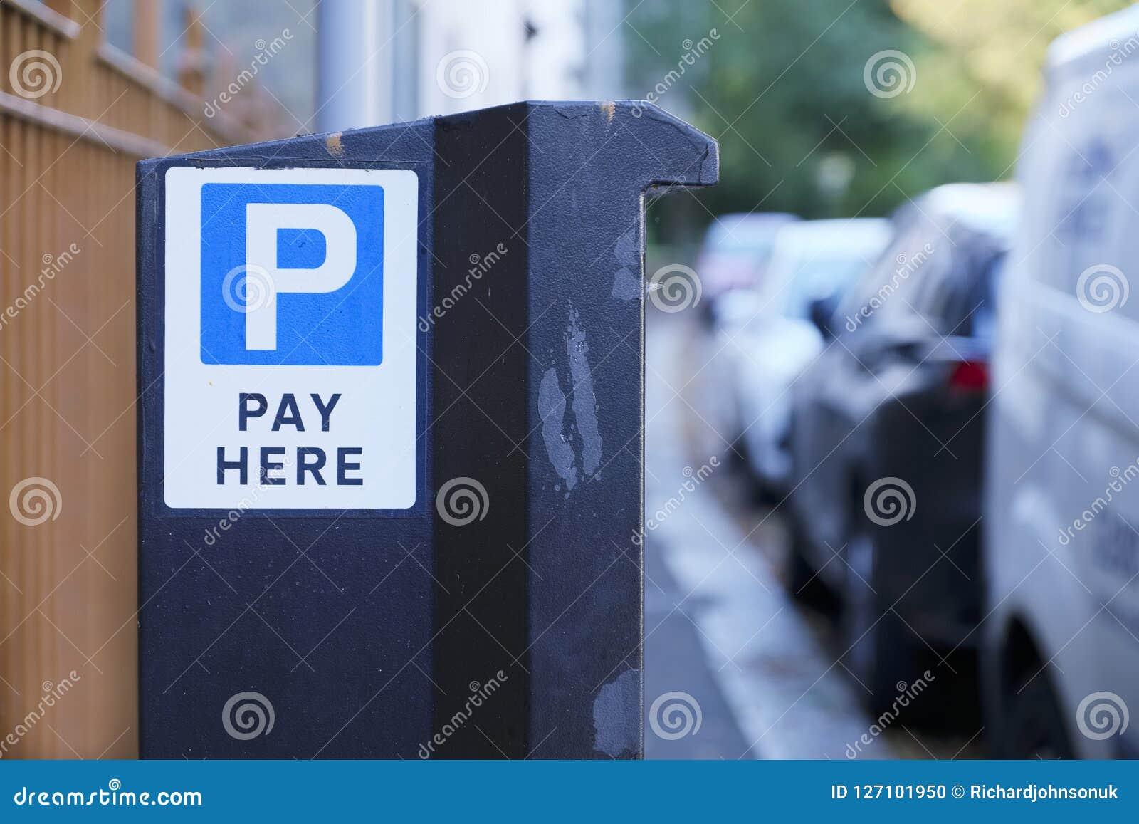 Πληρώστε εδώ τη μηχανή χώρων στάθμευσης αυτοκινήτων στην οδό και τη σειρά των οχημάτων έξω από τα σπίτια