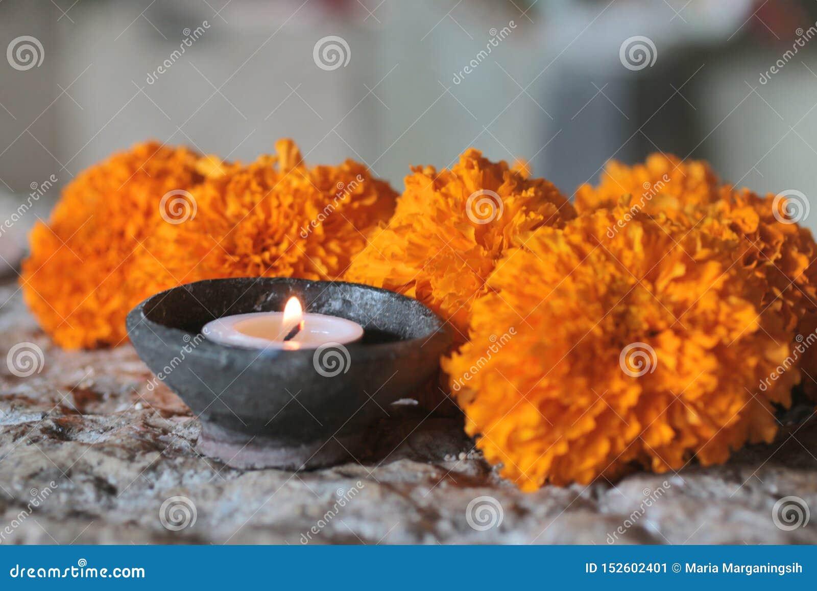 Πνευματικότητα, SPA και μόνη έννοια θεραπείας Φως κεριών στα λουλούδια φυσικών κεραμικών κύπελλων και marigold