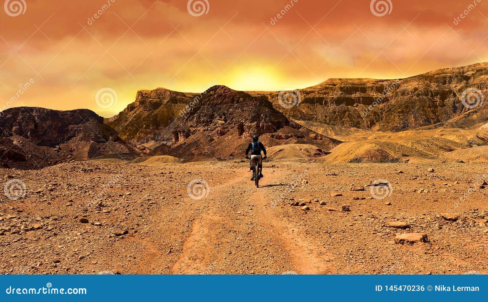 Ποδηλάτης βουνών στο ηλιοβασίλεμα σε μια έρημο