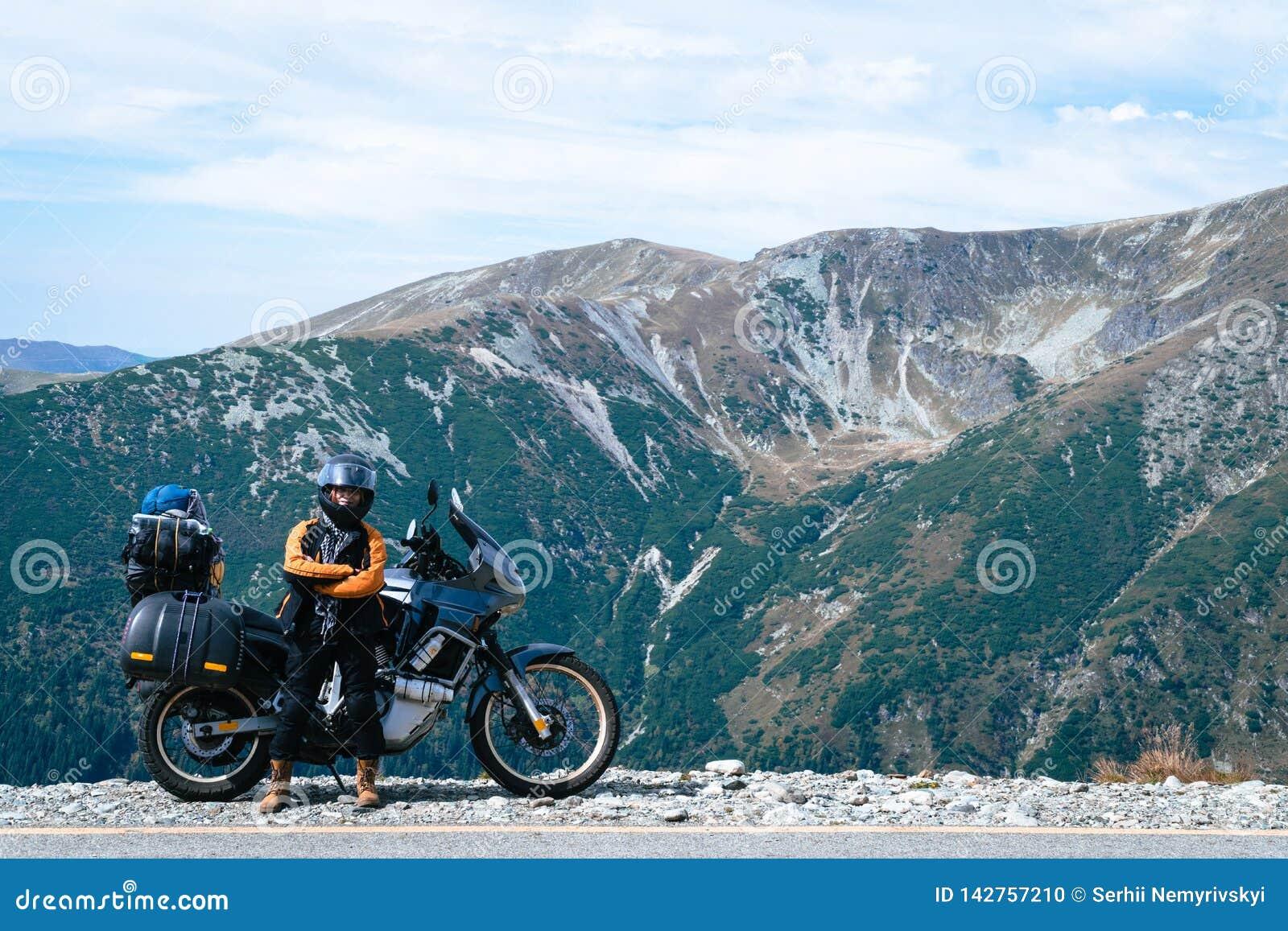 Ποδηλάτης γυναικών και τοπ δρόμος βουνών μοτοσικλετών adveture Ταξίδι, διακοπές στην Ευρώπη, τρόπος μοτοσυκλετιστών, τουρισμός, T