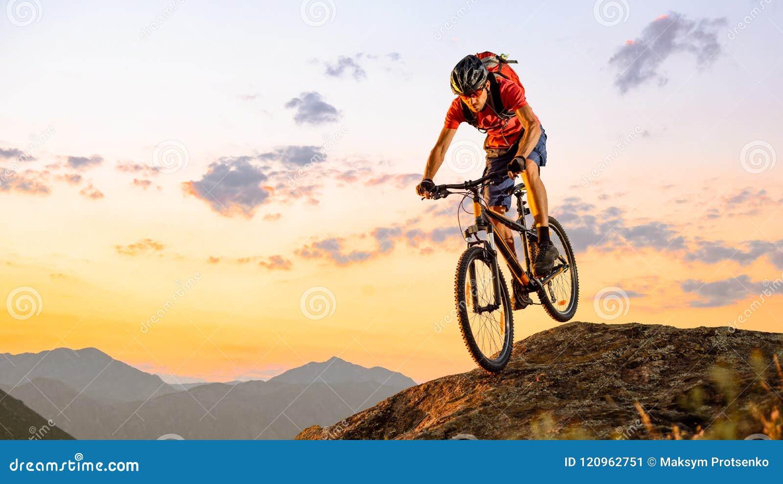 Ποδηλάτης στο κόκκινο που οδηγά το ποδήλατο κάτω από το βράχο στο ηλιοβασίλεμα Ακραίος αθλητισμός και έννοια Enduro Biking