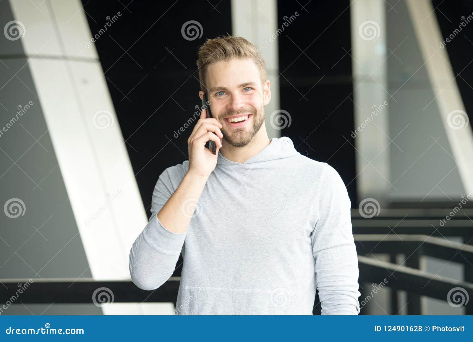 Ποιες μεγάλες ειδήσεις Άτομο με το αστικό υπόβαθρο smartphone κλήσης γενειάδων Ευτυχές smartphone χρήσης χαμόγελου τύπων για να ε