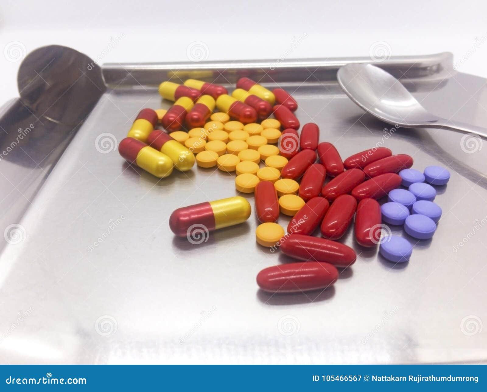 Πολλά ζωηρόχρωμο φάρμακο και ασημένιο κουτάλι είναι σε έναν ασημένιο δίσκο για το cou