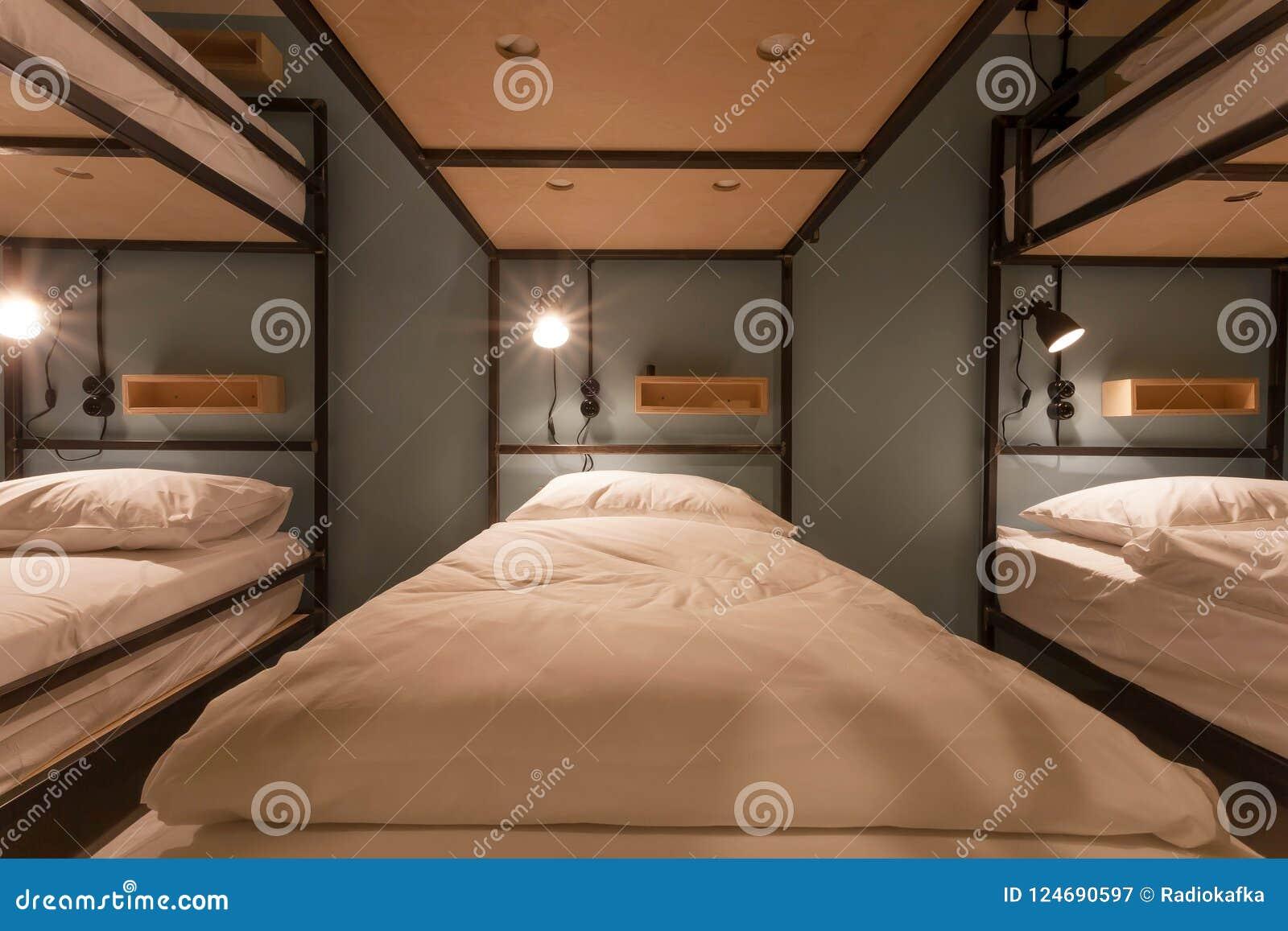 Πολλά κρεβάτια κουκετών μέσα σε ένα δωμάτιο dorm του τουριστικού ξενώνα με τα καθαρά κρεβάτια