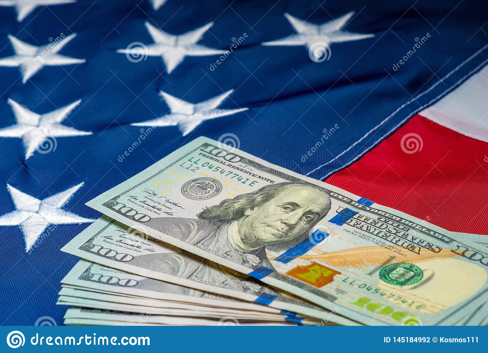 πολλά χρήματα 100 δολάρια στο υπόβαθρο της αμερικανικής σημαίας