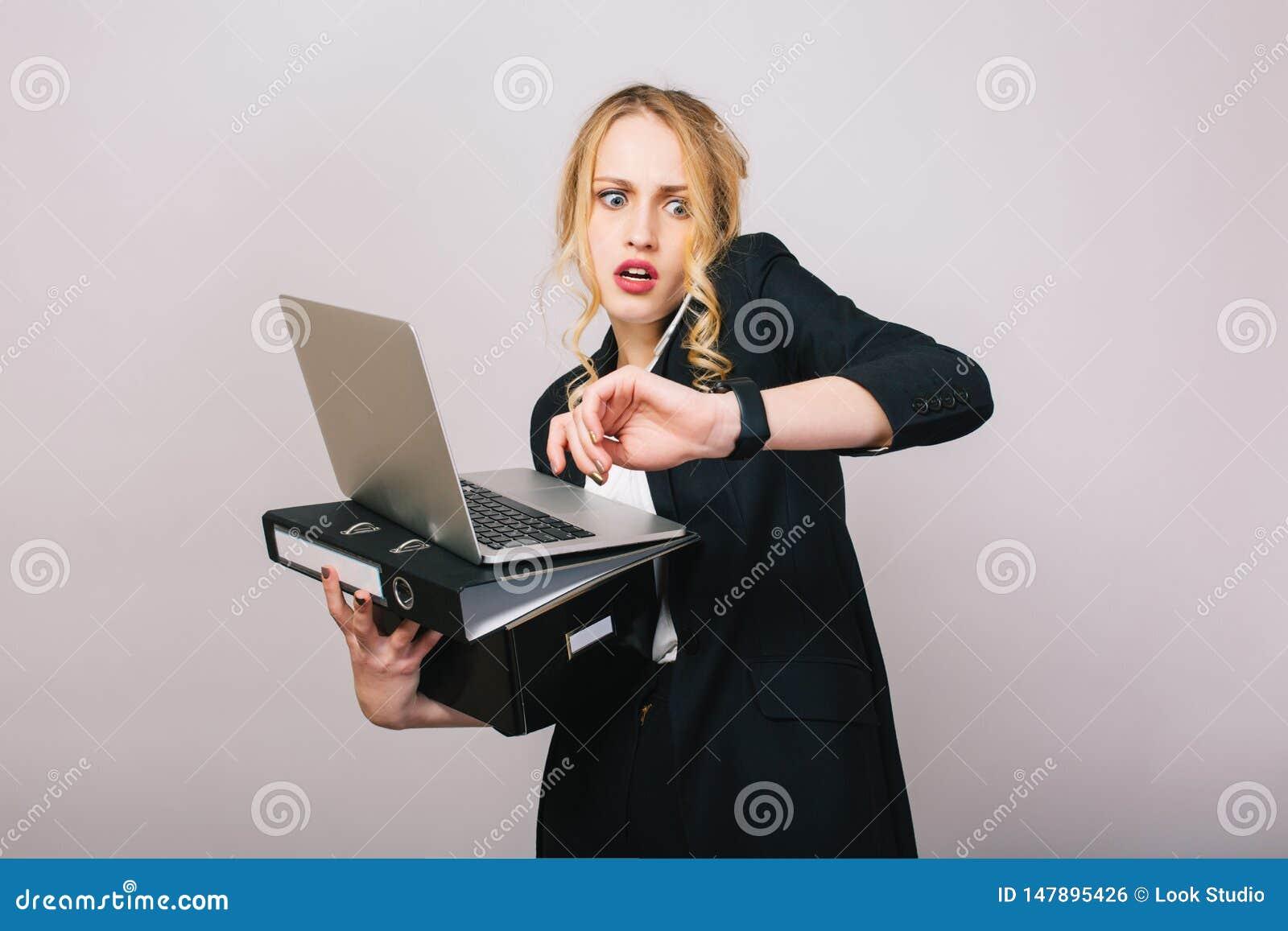 Πολυάσχολος χρόνος γραφείων εργασίας της ξανθής νέας γυναίκας στα επίσημα ενδύματα με το lap-top, φάκελλος που μιλά στο τηλέφωνο