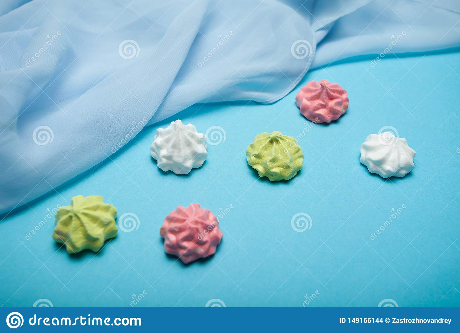 Πολυ χρωματισμένη γλυκιά παραδοσιακή μορφή μαρέγκας που απομονώνεται στο μπλε υπόβαθρο